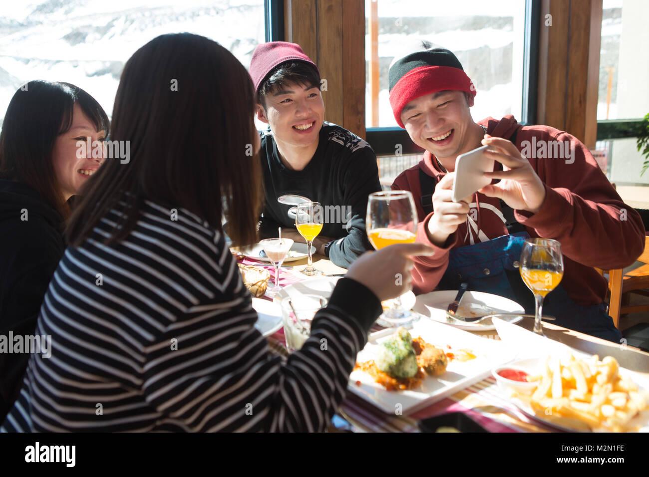 Junge Männer und Frauen im Restaurant zum Abendessen. Stockbild