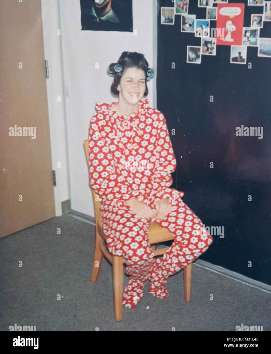 Teenager mit Rollen in ihrem Haar zu tragen One-Piece Footed Pajamas, USA Stockfoto
