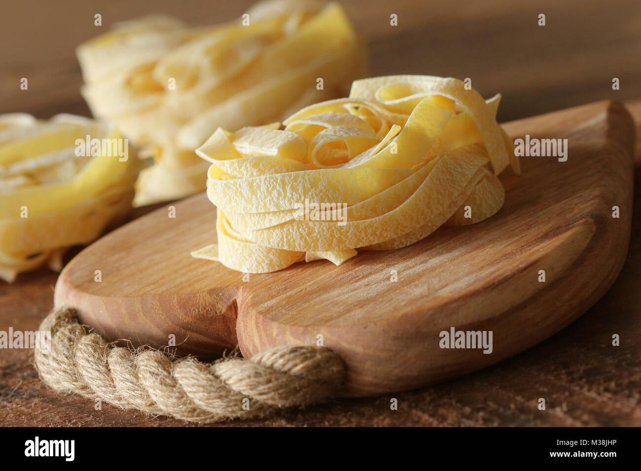 Nest von Pasta tagliatelle auf Holz Schneidebrett aon rustikalen Hintergrund. Selektiver Fokus Stockbild