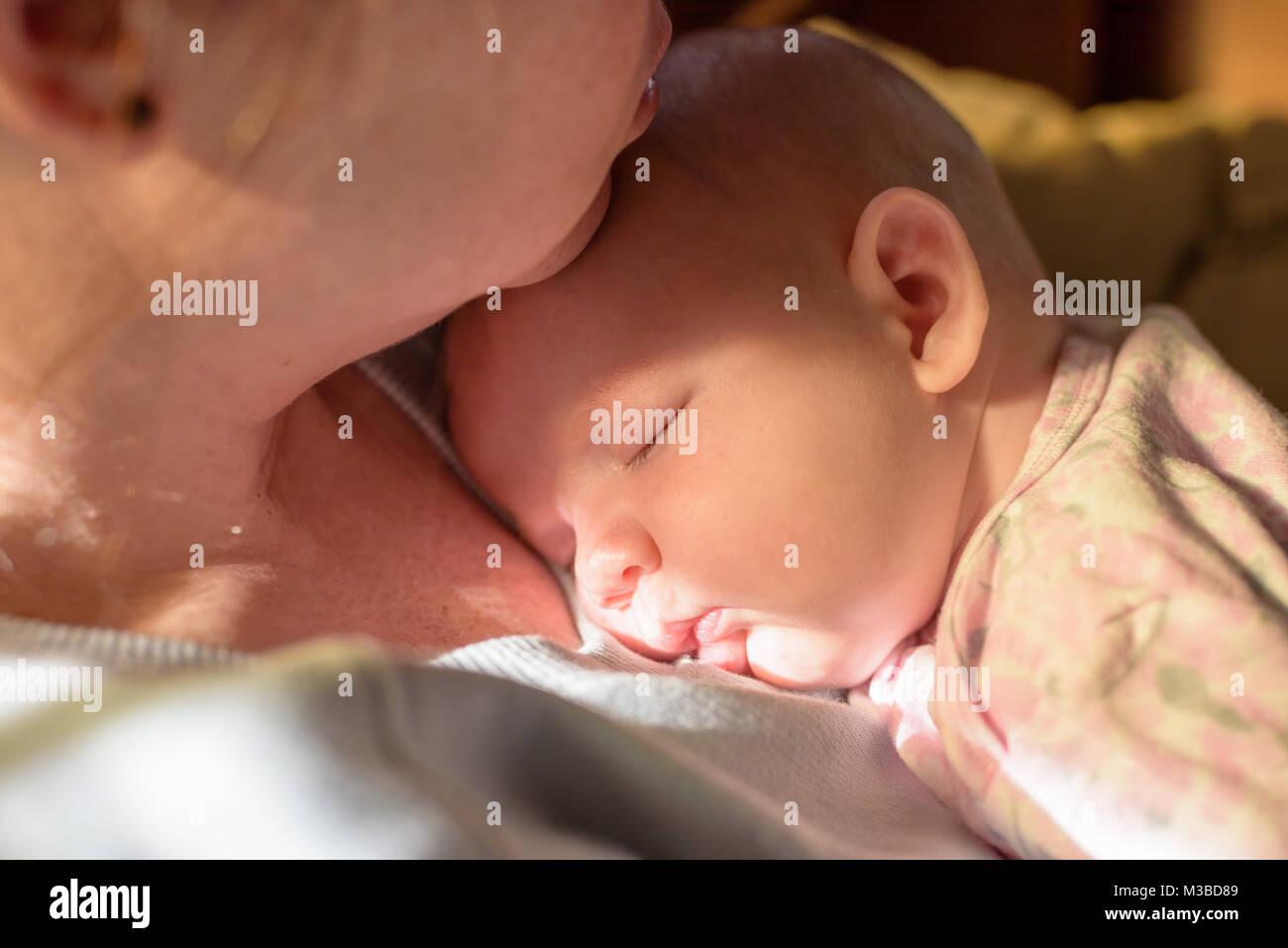 Junge Mutter sitzen auf der Couch kuscheln ein schlafendes Neugeborenes im Morgenlicht. Stockfoto