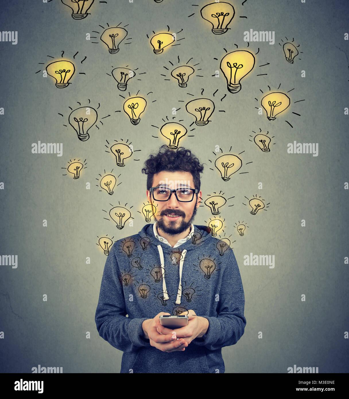 Junger Mann in Brillen holding Smartphone und produzieren viele erfolgreiche Ideen. Stockbild