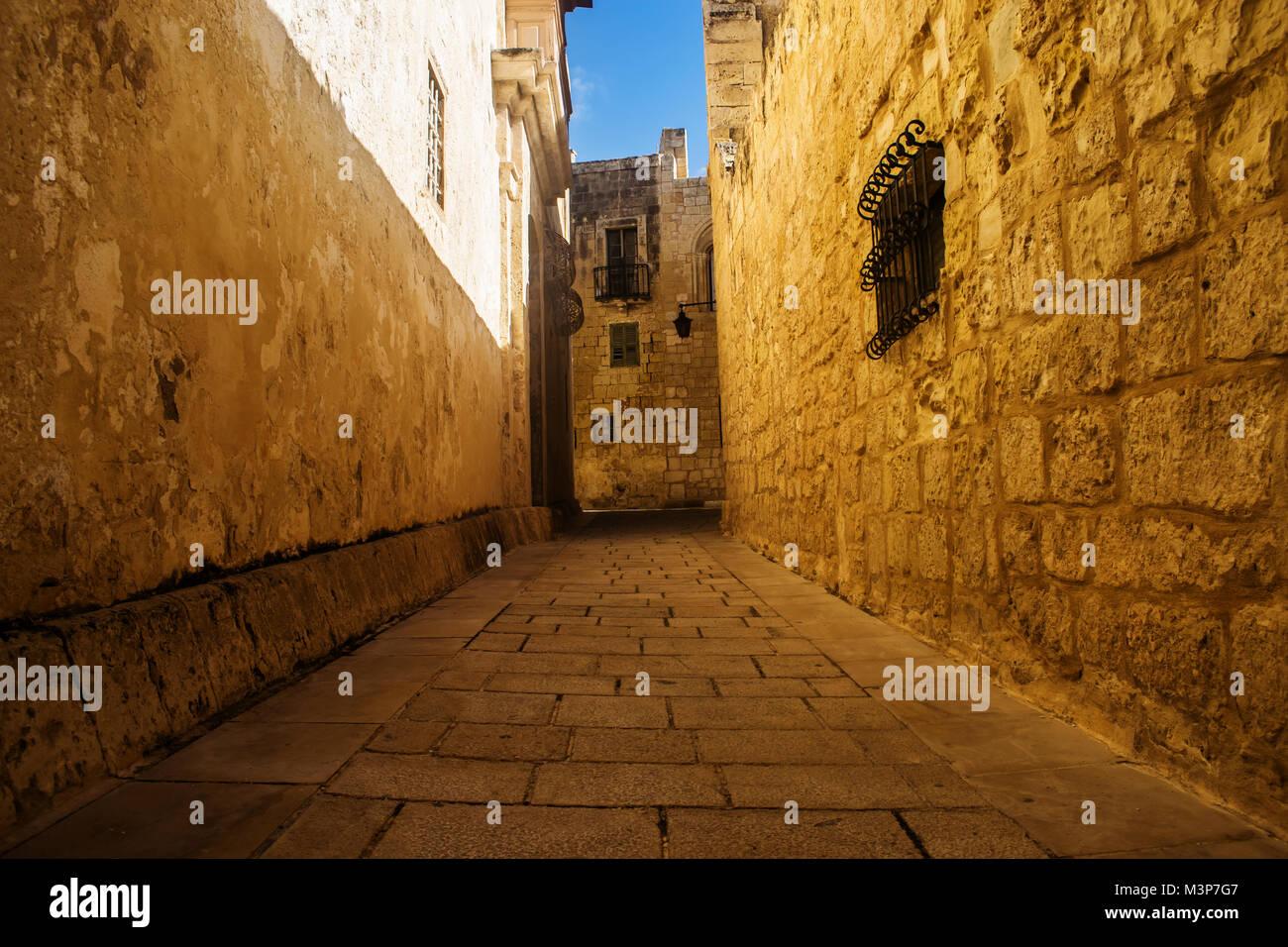 Einer typischen schmalen und historische Straße mit Kopfsteinpflaster Wände in Mdina, Malta. Stockbild