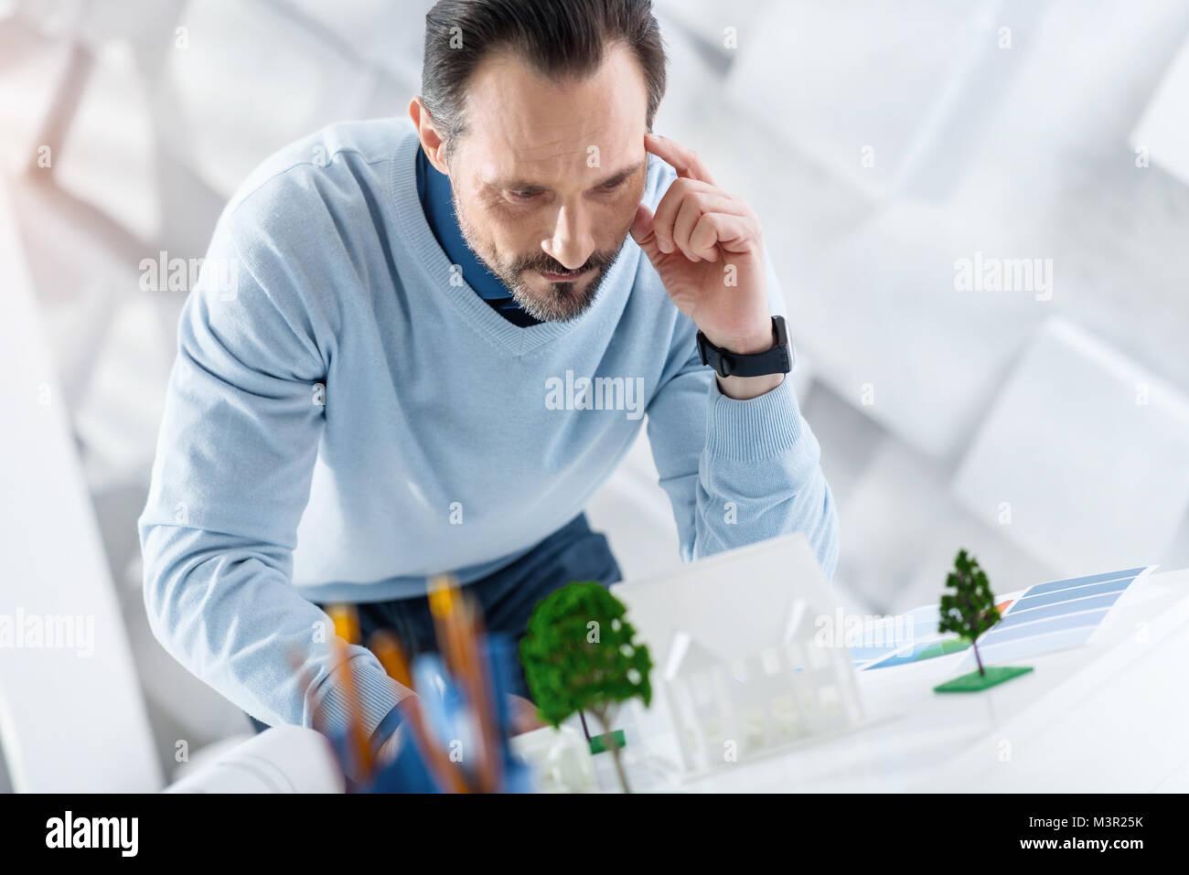 Nachdenklich Architekt am Modell eines Hauses suchen Stockbild