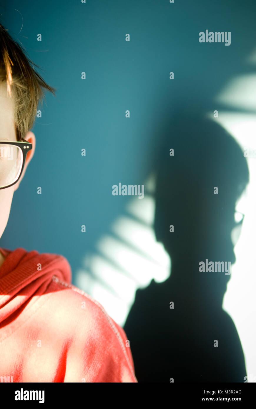 Moody und atmosphärischen 7/8 Ansicht von zehn Jahre alten jungen Gesicht mit Brille mit seinem Schatten fällt Stockbild