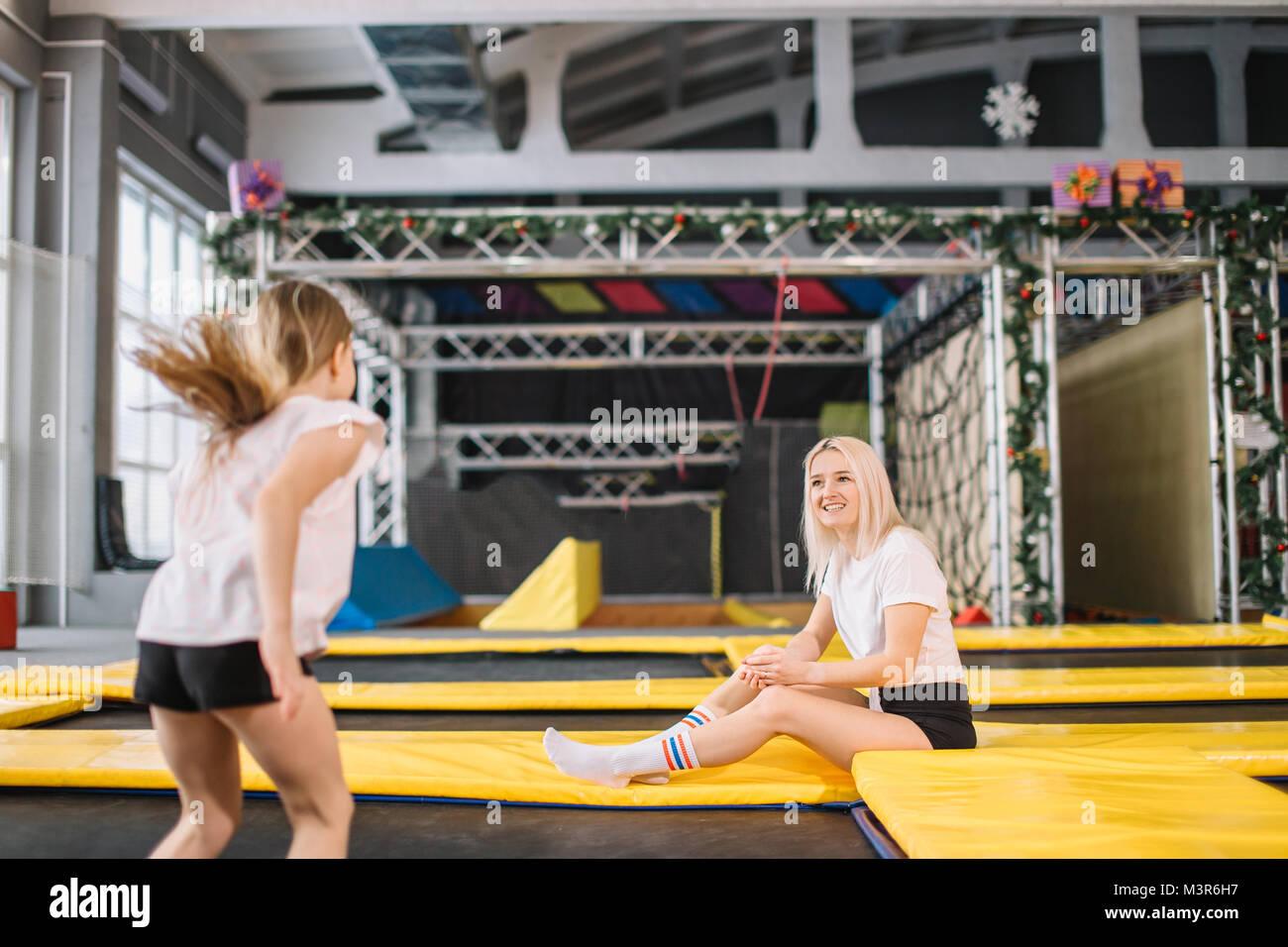 Die Tochter springt auf einem Trampolin, während Mutter watch für Sicherheit Stockbild