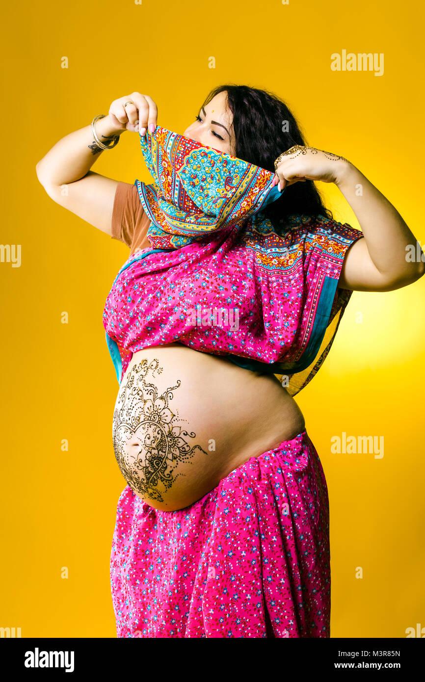 Gerne schwangere Frau in der indischen Sari, Bauch und Hände mit Henna bemalt Stockfoto