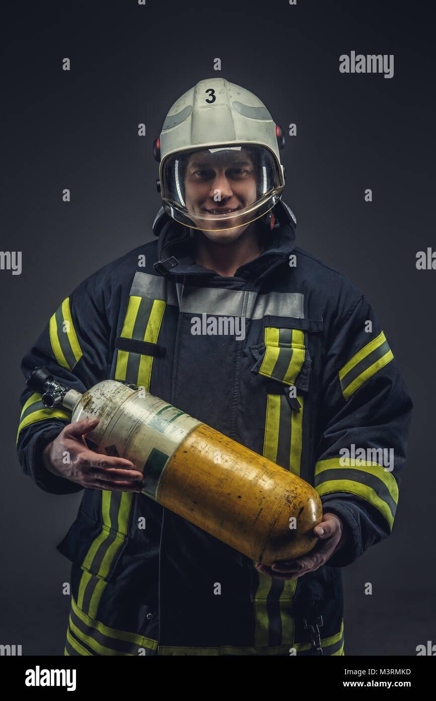 Feuerwehrmann rescue hält gelb Sauerstoff tank. Stockbild