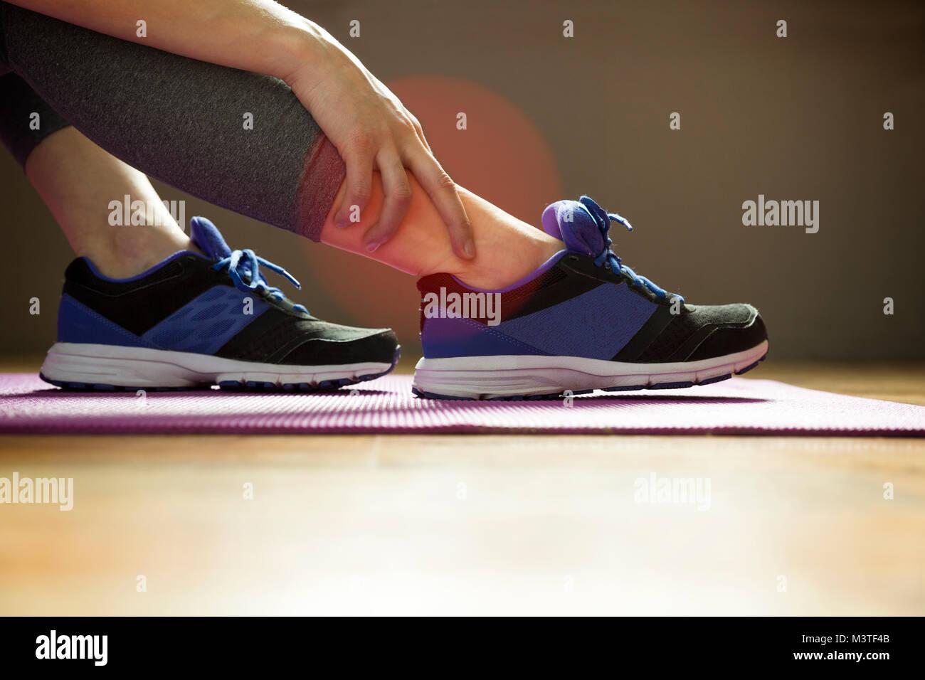 Junge Frau mit einer Knöchelverletzung beim Trainieren. Sport Übung Verletzungen Konzept. Stockfoto