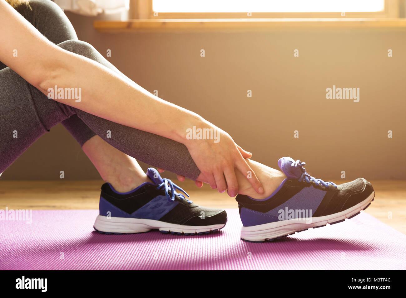 Junge Frau mit einer Knöchelverletzung beim Trainieren. Sport Übung Verletzungen Konzept. Stockbild