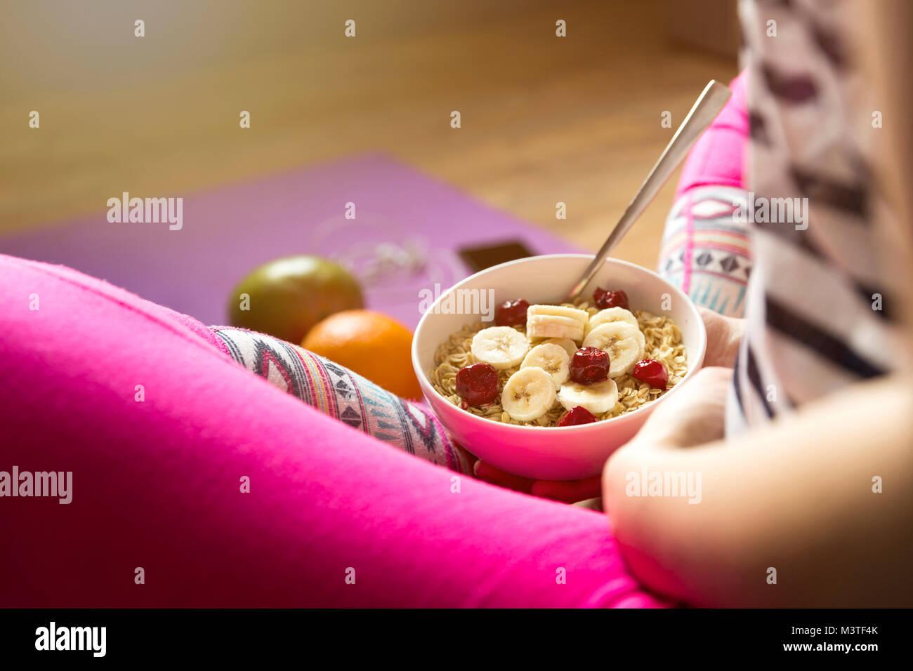 Junge Mädchen essen ein Müsli mit Beeren nach dem Workout. Fitness und gesunde Lebensweise. Stockbild