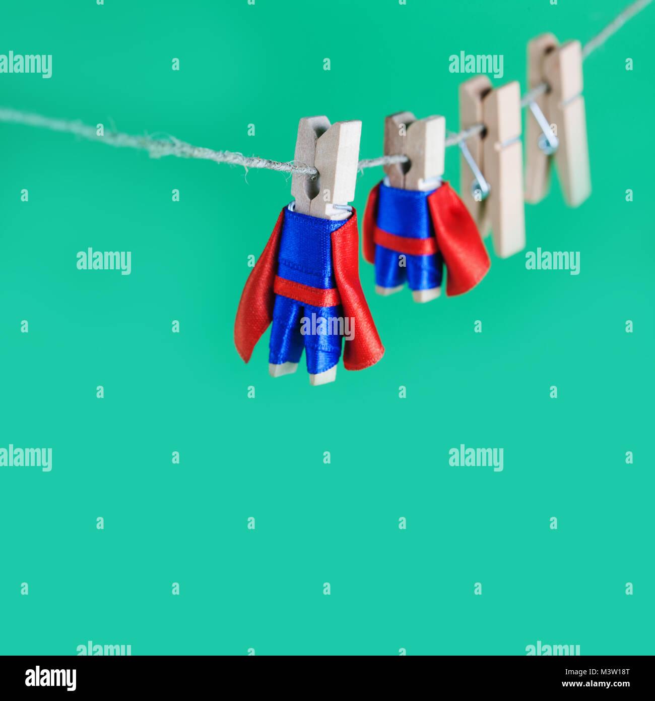 Mutigen Superhelden Wäscheklammern aus Holz. Teamleiter Zeichen in blauen Anzug roten Cape. grüner Hintergrund, Stockbild