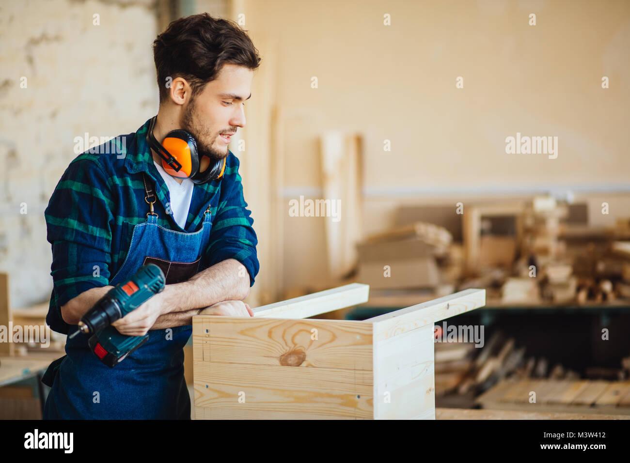 Junge männliche Tischler in der Werkstatt bei Camera suchen Stockbild