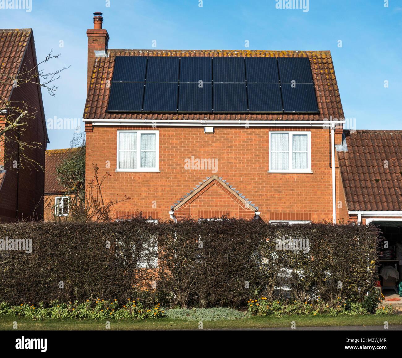 Solar Panels in direktem Sonnenlicht, der warf/abfallenden Dach eines modernen Einfamilienhauses angebracht. Langtoft, Stockbild