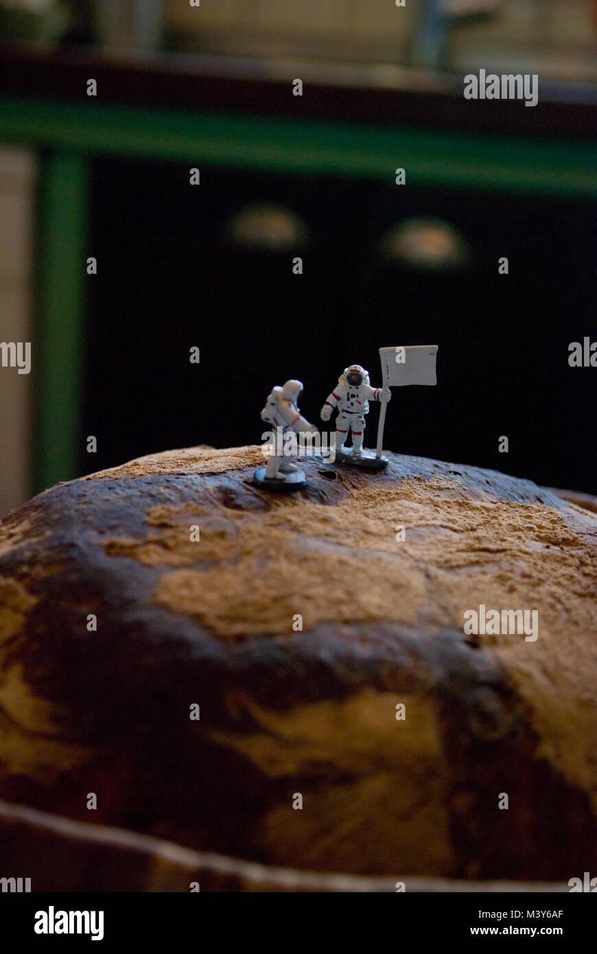 Zwei toy Astronaut zahlen, eine mit einer Fahne, auf den Gipfel eines frisch gebackenen Sauerteig Brot, ähnlich Stockbild