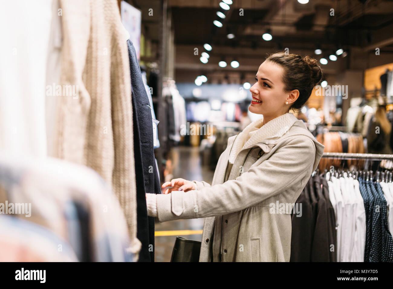 Junge attraktive Frau kaufen Kleidung in der Mall Stockbild