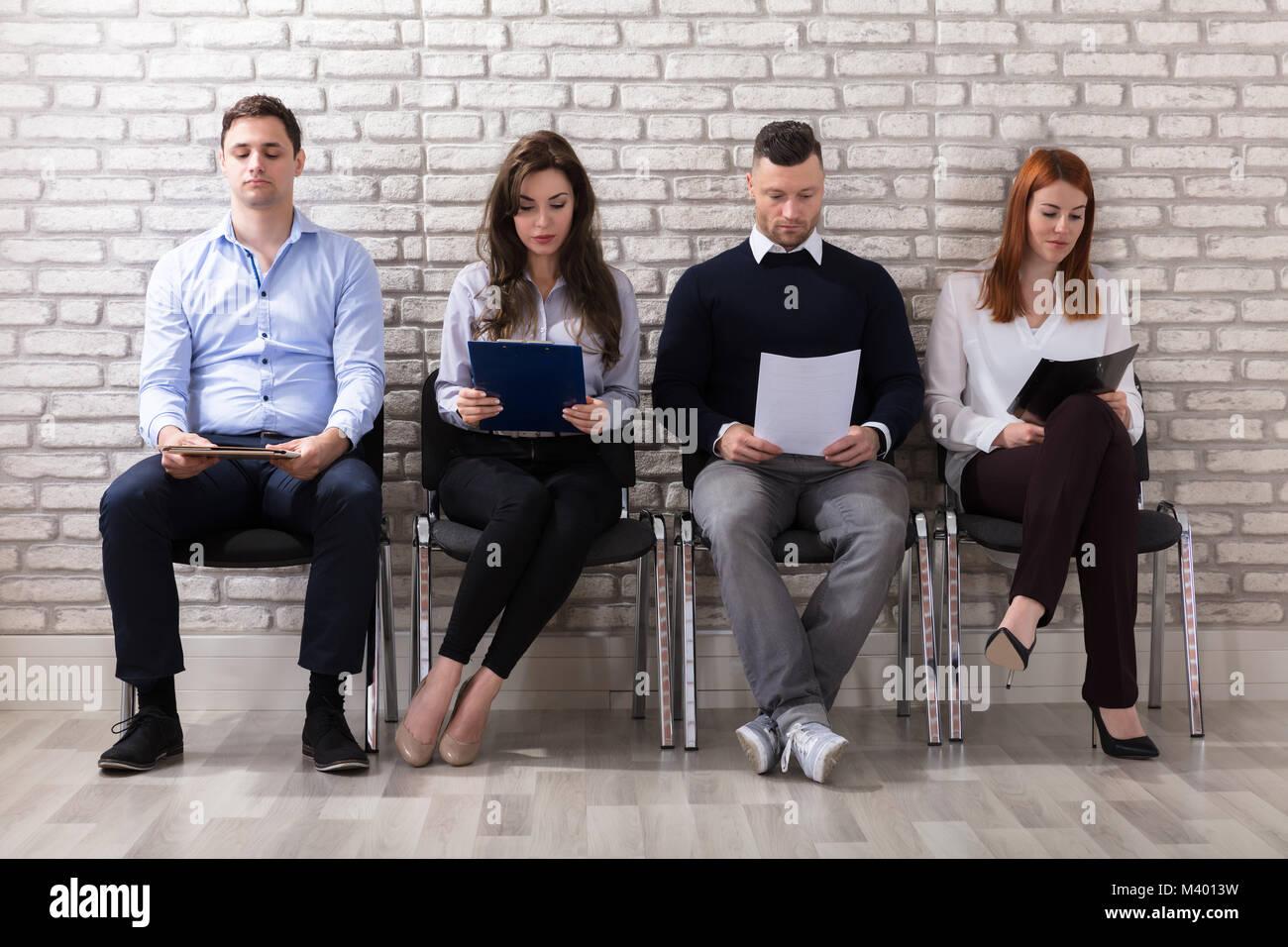 Gruppe von Menschen sitzen auf Stuhl warten auf Job Interview im Büro Stockbild