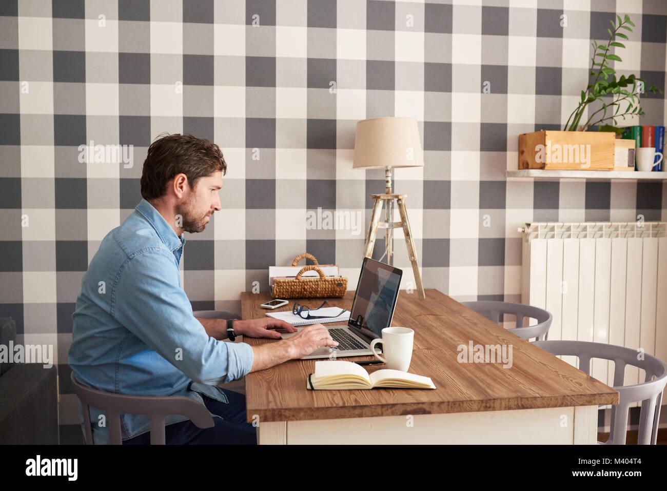 Junger Mann in seinem Wohnzimmer auf einem Laptop arbeiten Stockbild