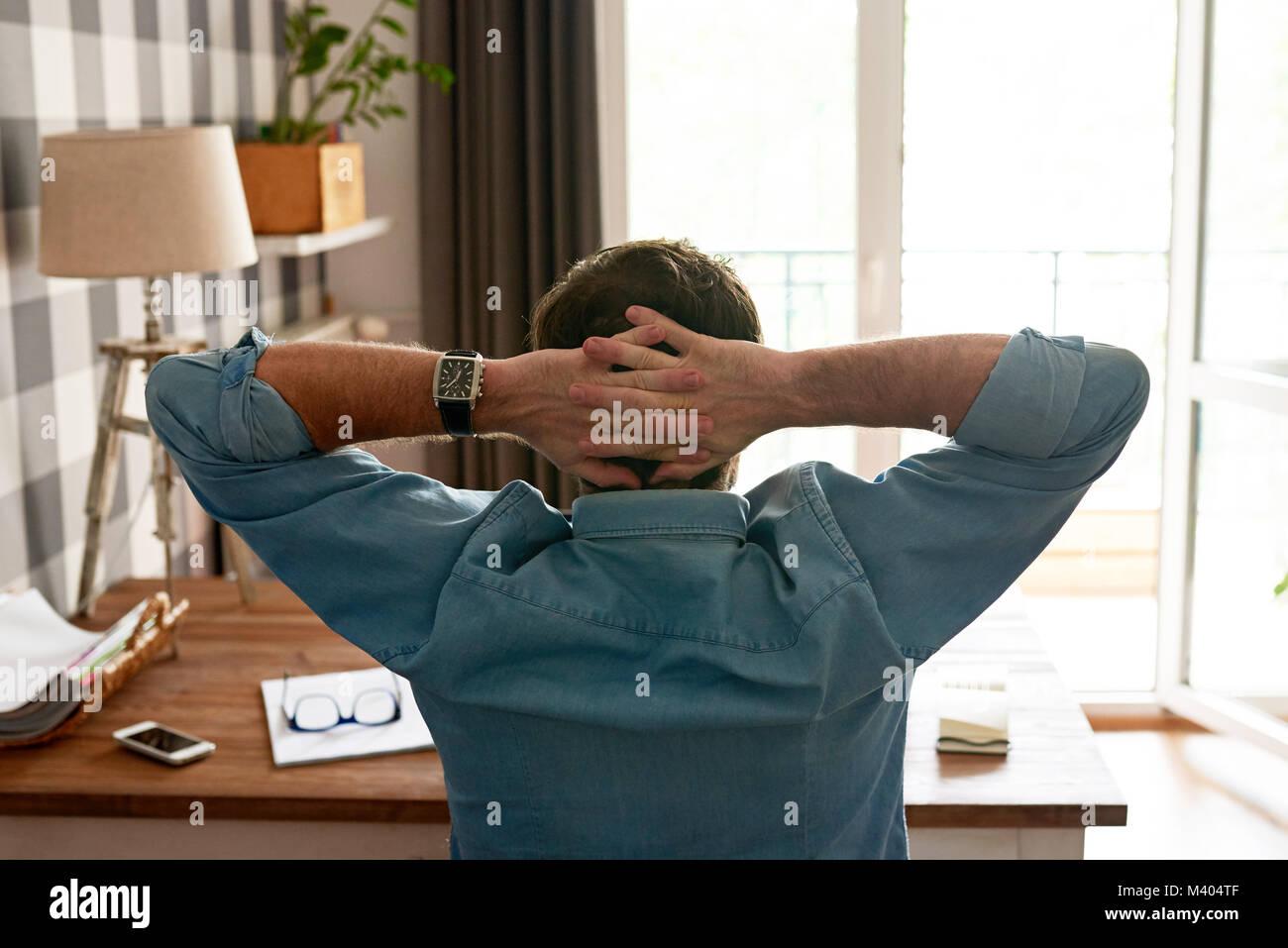 Mann lehnte sich in seinem Stuhl zurück, während die von zu Hause aus arbeiten Stockbild