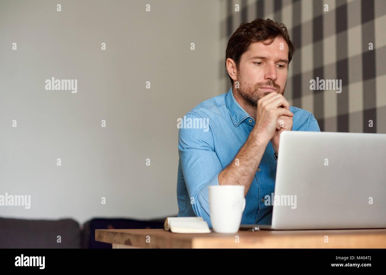 Junger Mann, der an einem Notebook arbeitet in seinem Wohnzimmer Stockbild