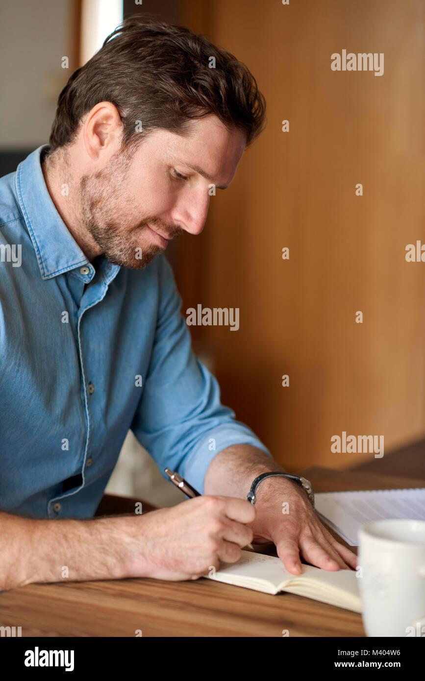 Junger Mann schreiben in einem Notebook während der Arbeit von zu Hause aus Stockbild