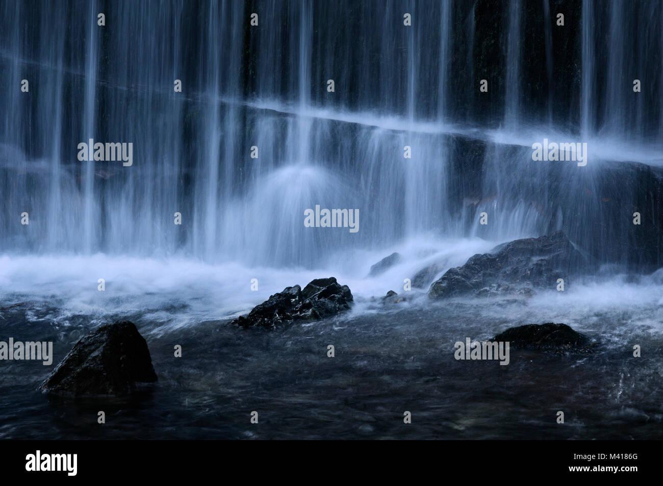 Teilweise eingetaucht Felsen inmitten der Mächtigen ethereal Fluss von einem Wasserfall. Stockbild