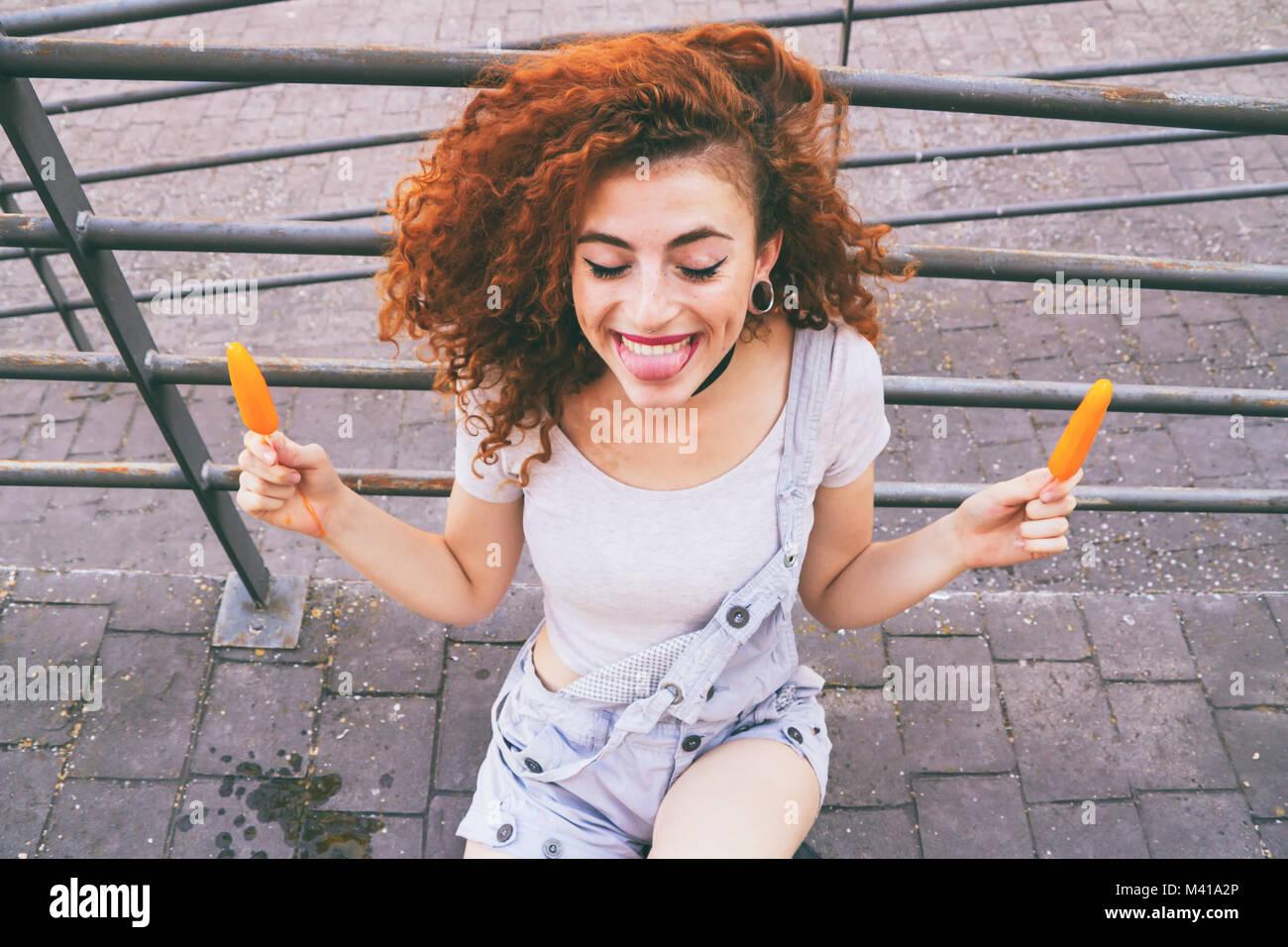 Rothaarige junge Frau essen Eis im Sommer Stockbild