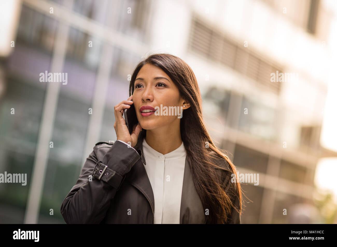 Frau mit Smartphone zu Fuß in der Stadt Stockbild