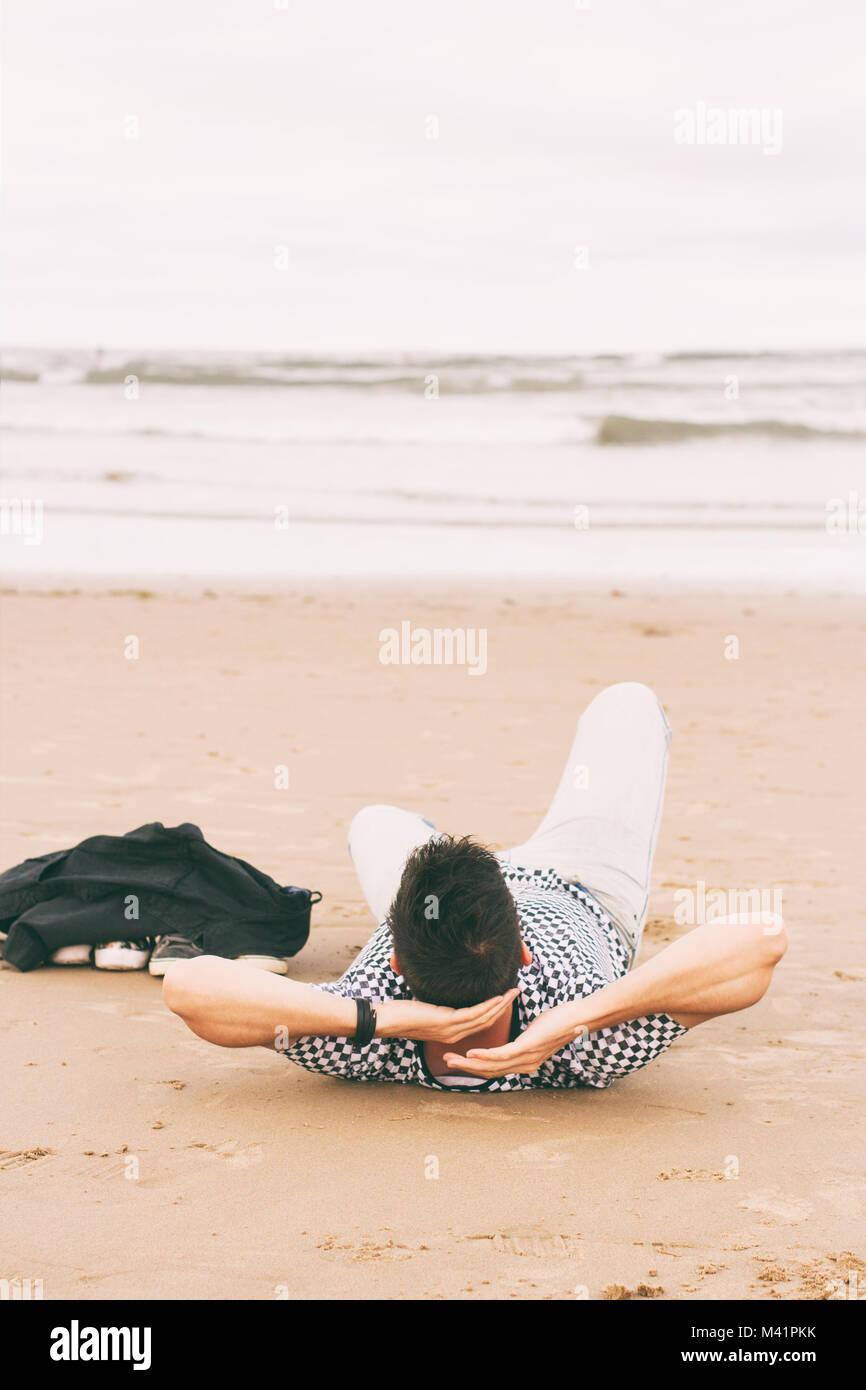 Junger Mann genießen Sie den Tag am Strand Stockbild