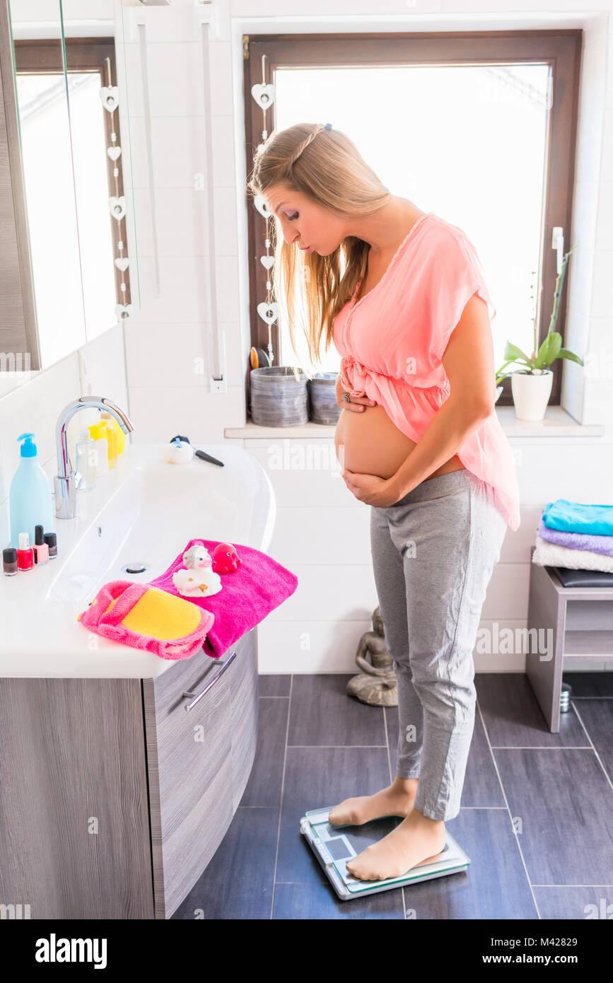 Schwangere Frau auf Waage im Badezimmer Stockbild