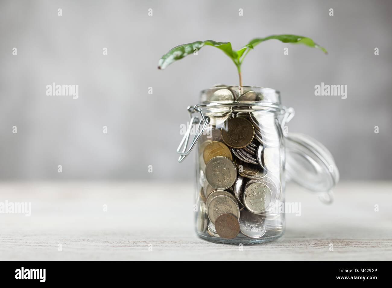 Münzen in einem Glas Stockbild