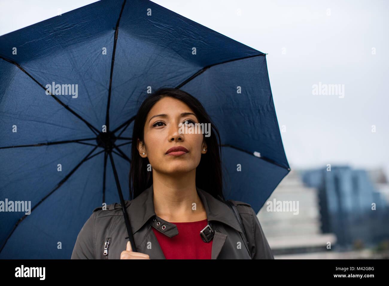 In der Stadt halten Regenschirm in schlechtem Wetter Geschäftsfrau Stockbild