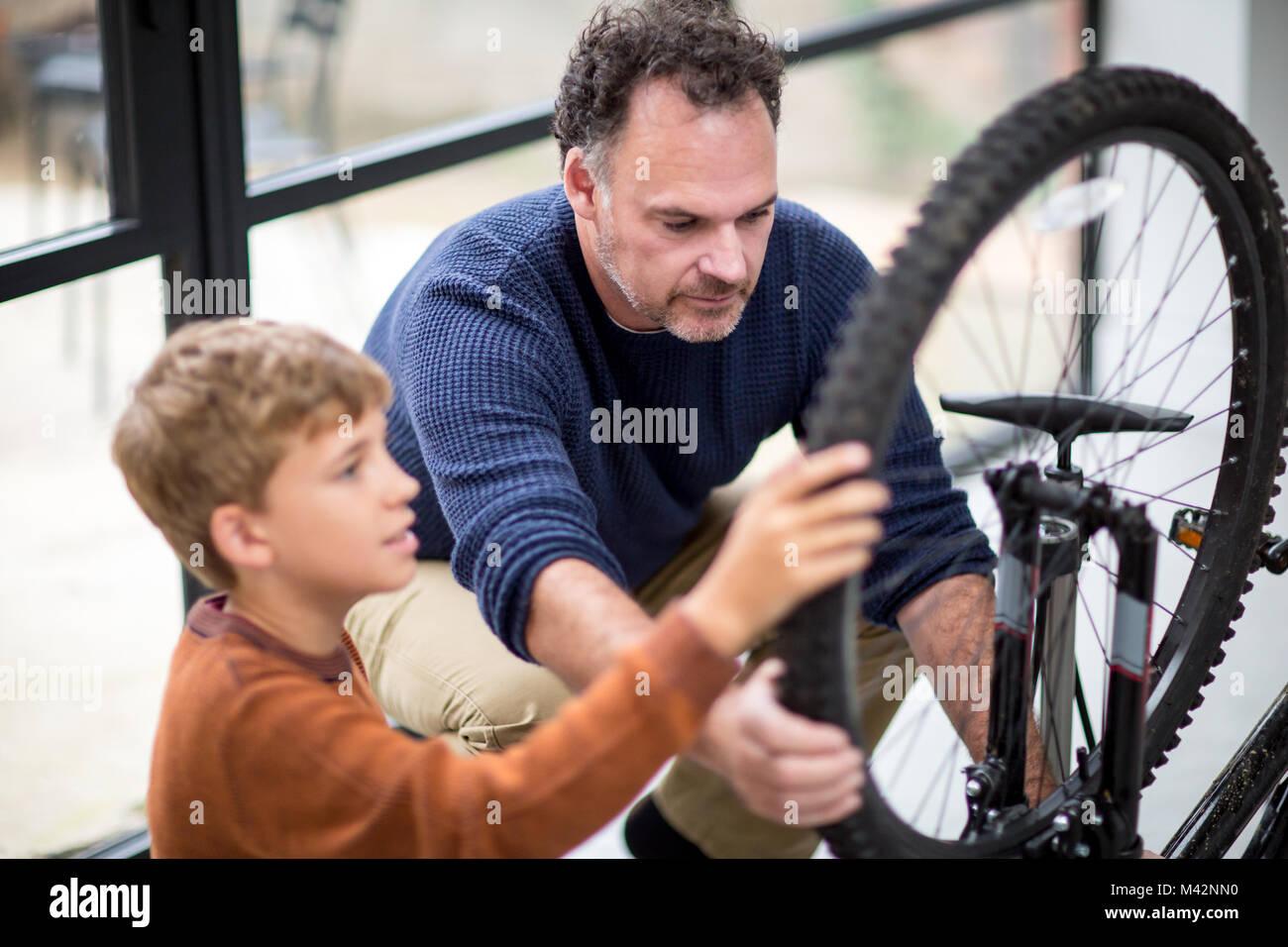Vater Sohn lehren, wie man für sein Fahrrad Stockbild