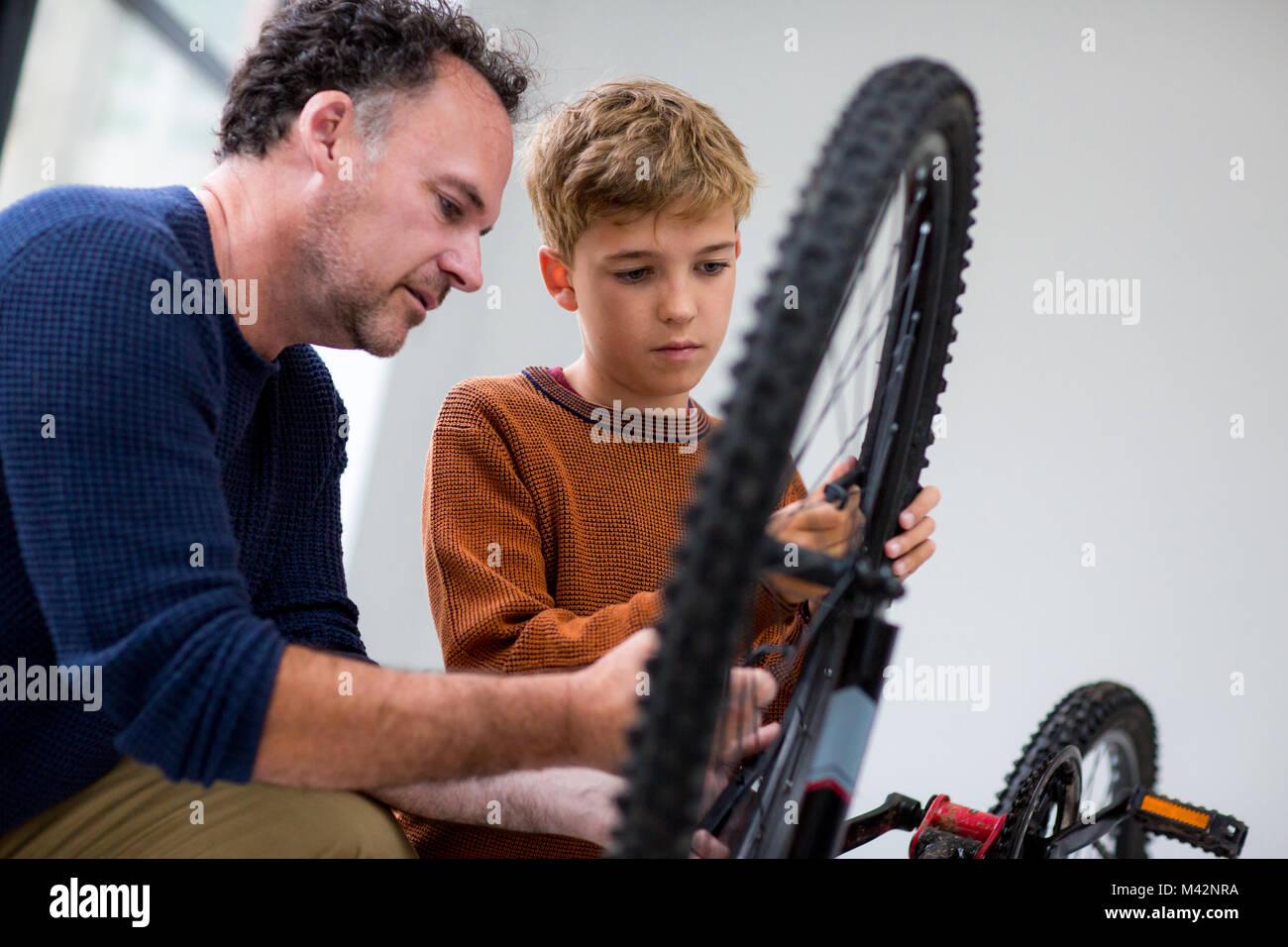 Junge Festsetzung Bike mit seinem Vati Stockbild