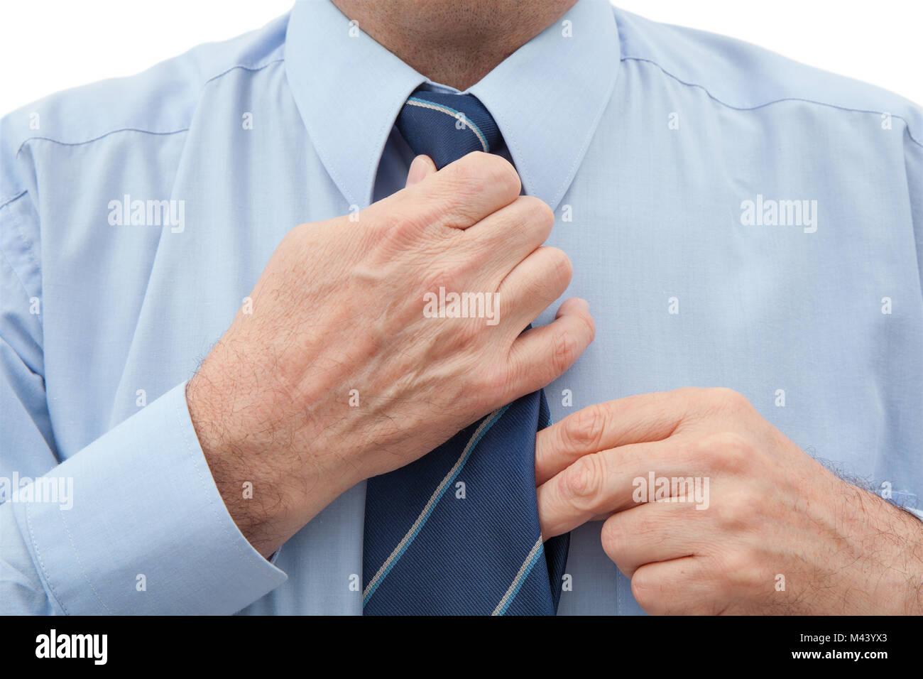 Geschäftsmann mit einem blauen Hemd einstellen eine gestreifte blaue Krawatte an seinem Hals Stockbild