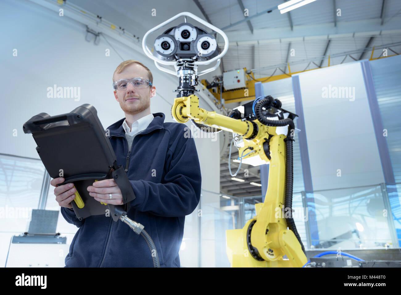 Portrait von Ingenieur mit Roboter in Robotics Research Facility Stockbild