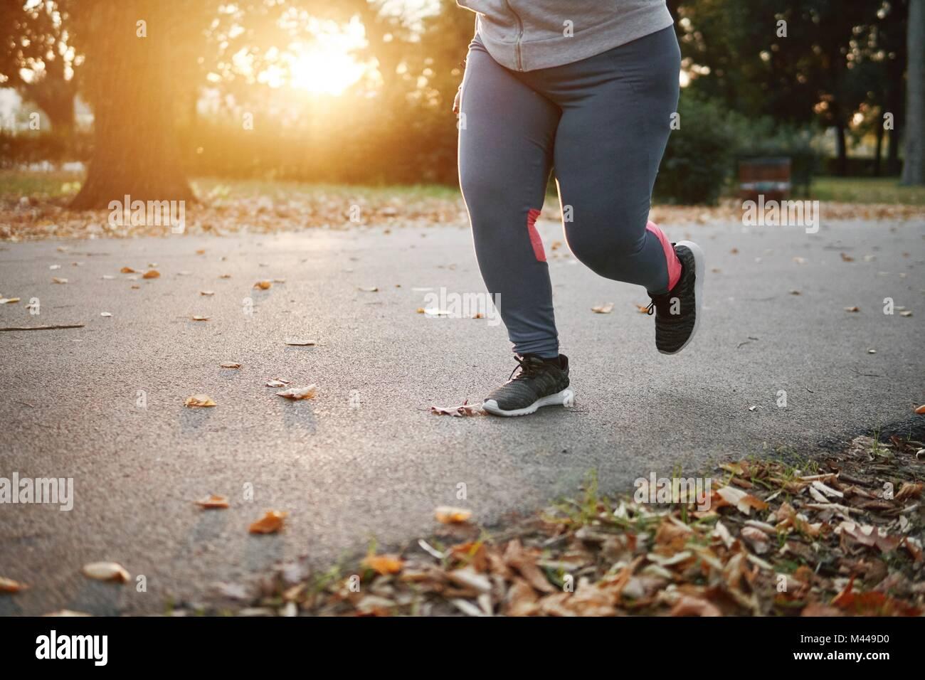 Kurvenreiche junge Läuferin im Park, an der Hüfte nach unten Stockbild