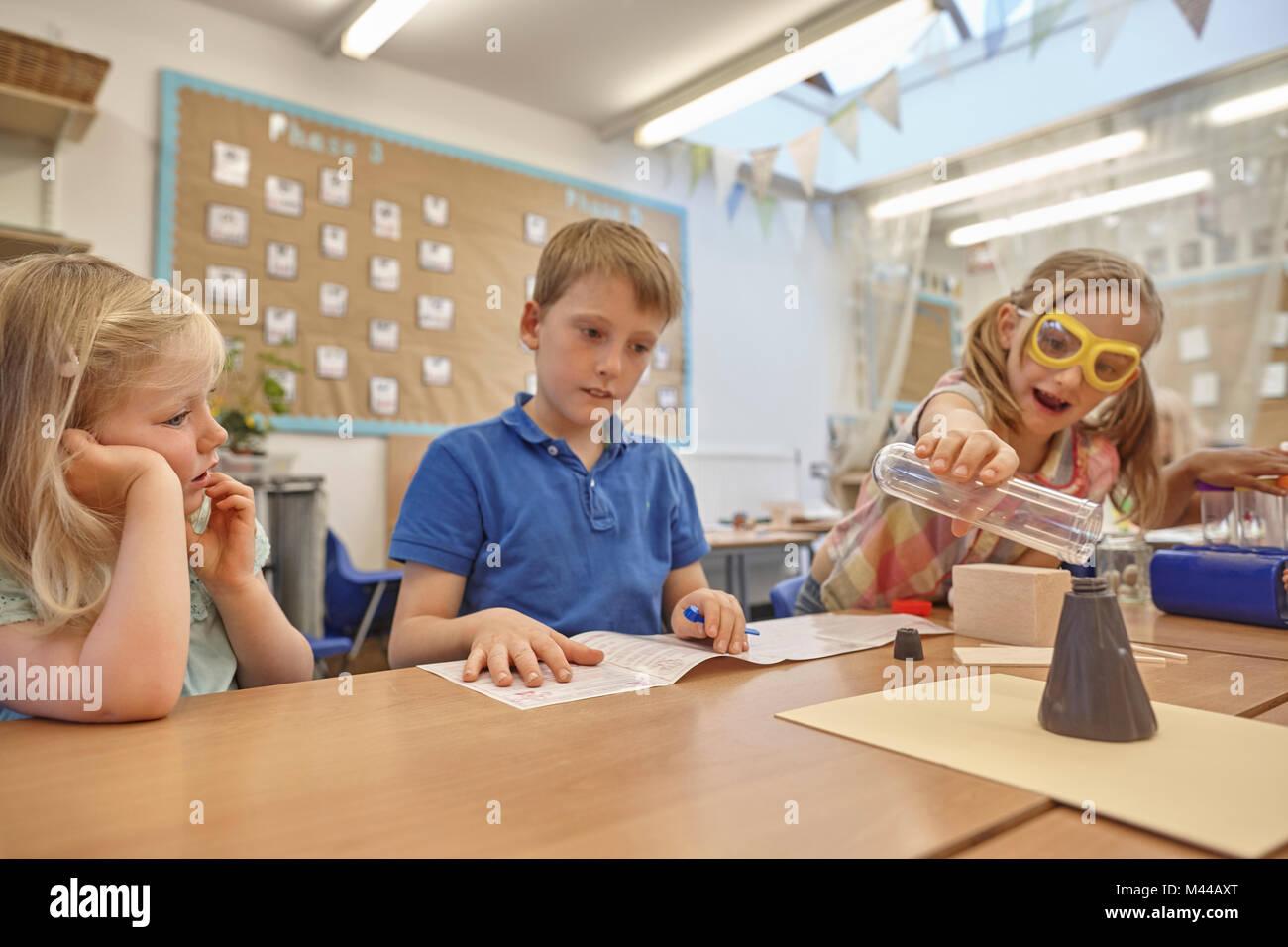 Primäre Schülerinnen und Junge tut Experiment im Klassenzimmer Schreibtisch Stockbild