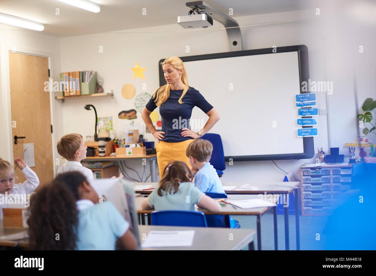 Lehrer mit den Händen auf den Hüften vor der Klasse in der Grundschule Stockbild