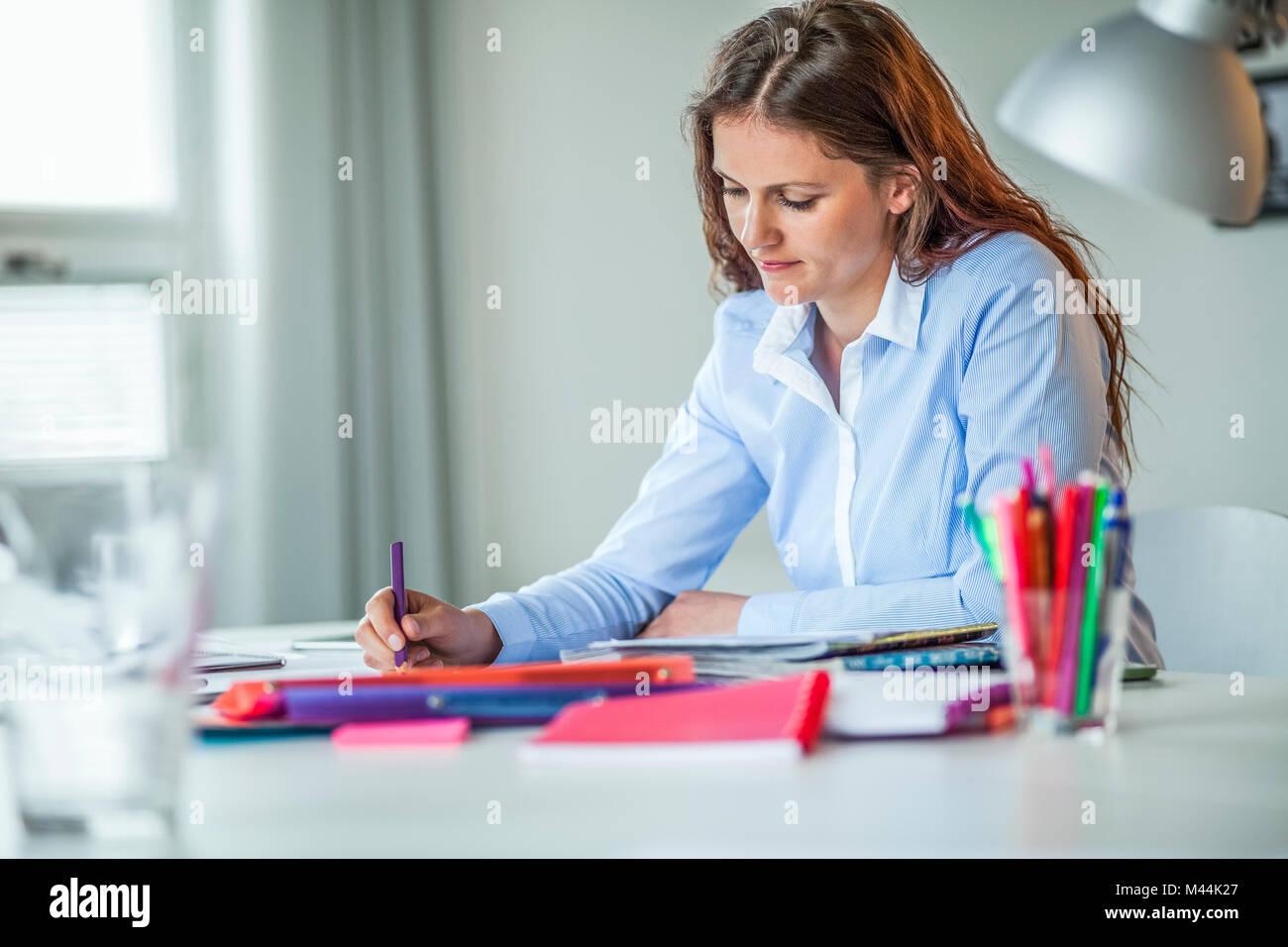 Junge weibliche Mode Designer am Schreibtisch im Büro arbeiten Stockbild