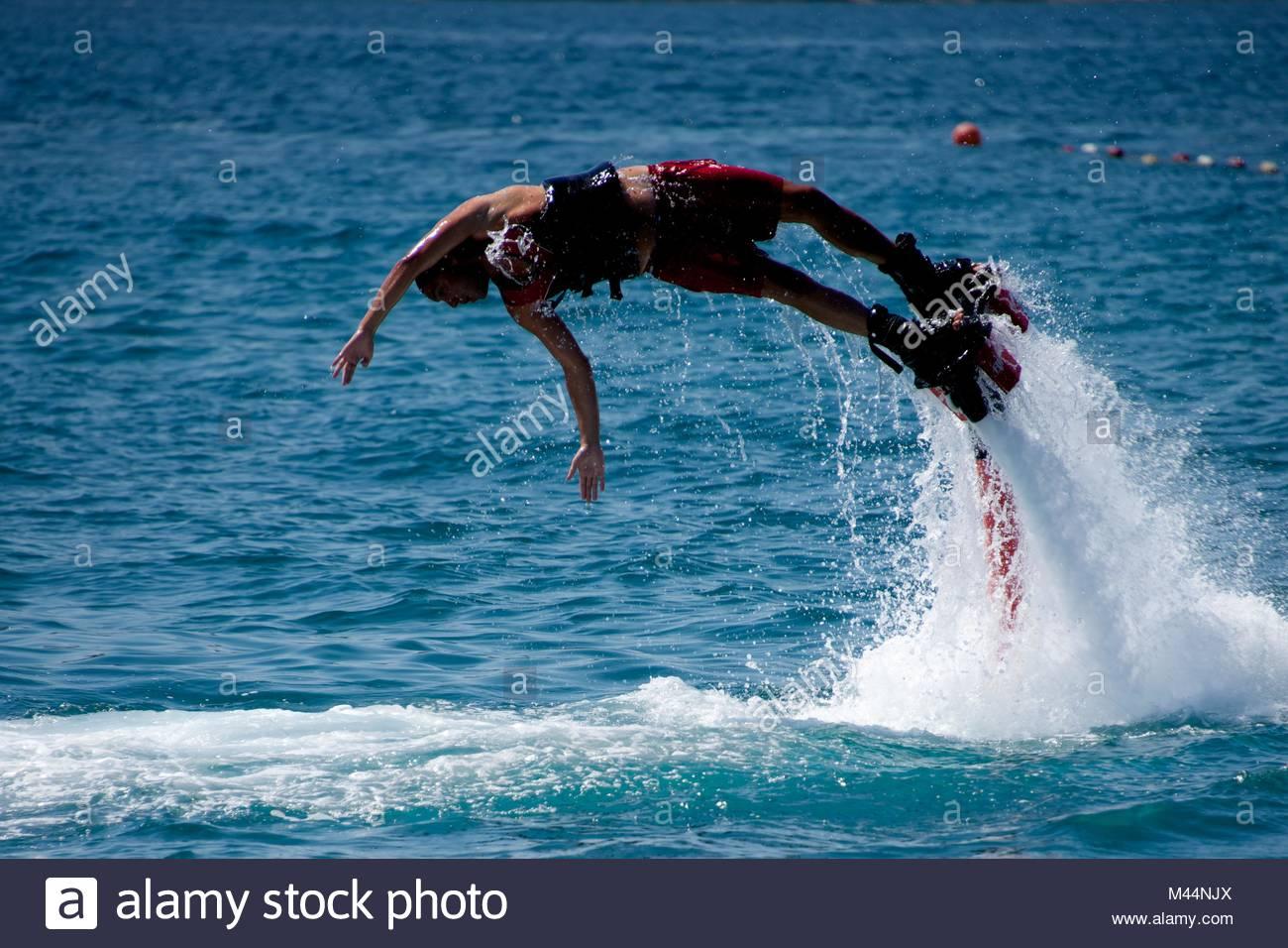 Flyboarder in Rot drehen horizontal in Tauchen Stockbild