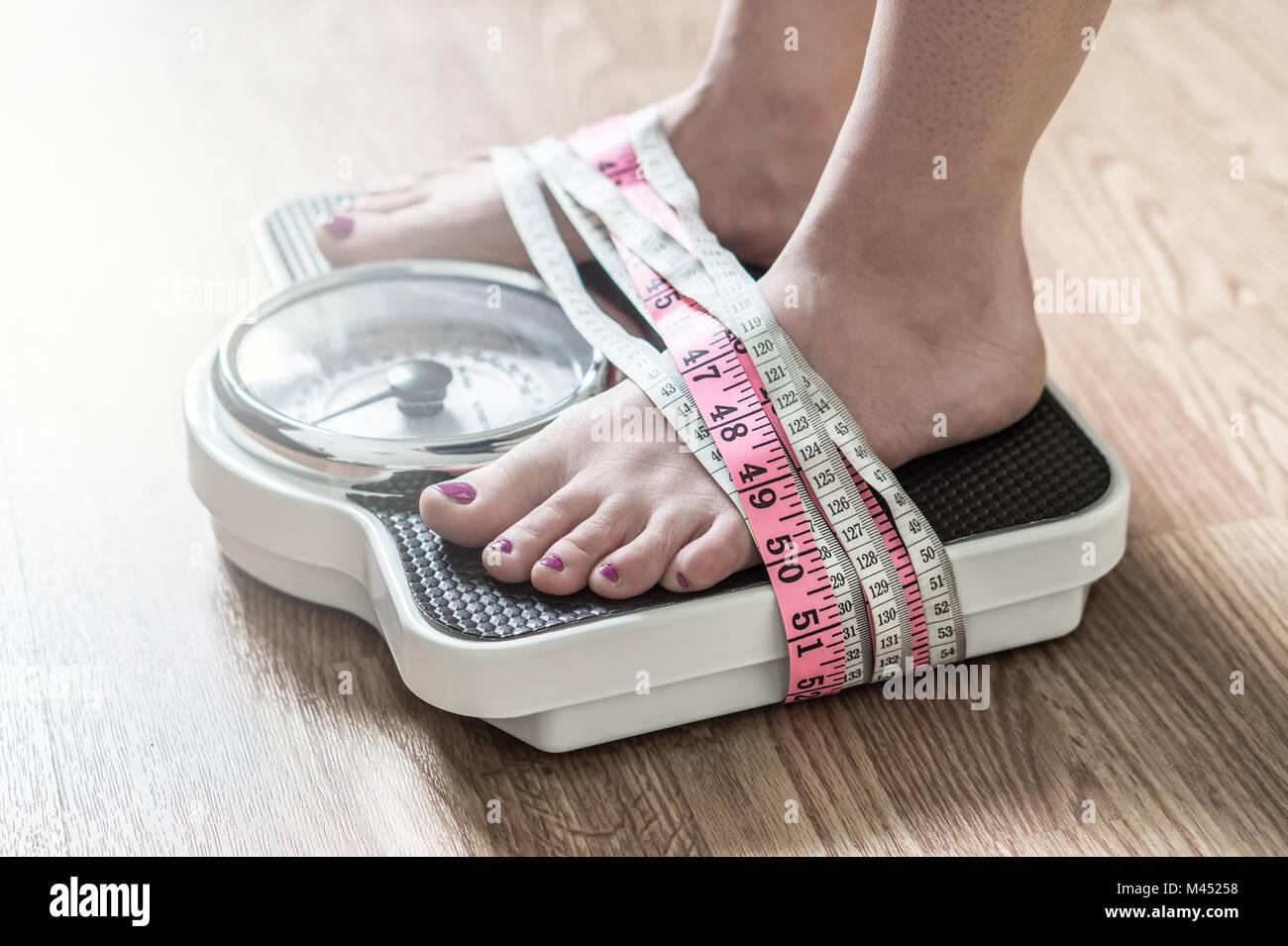 Magersucht und Essstörungen Konzept. Füße gefesselt mit Maßband auf eine Waage. Sucht und Besessenheit, Stockbild