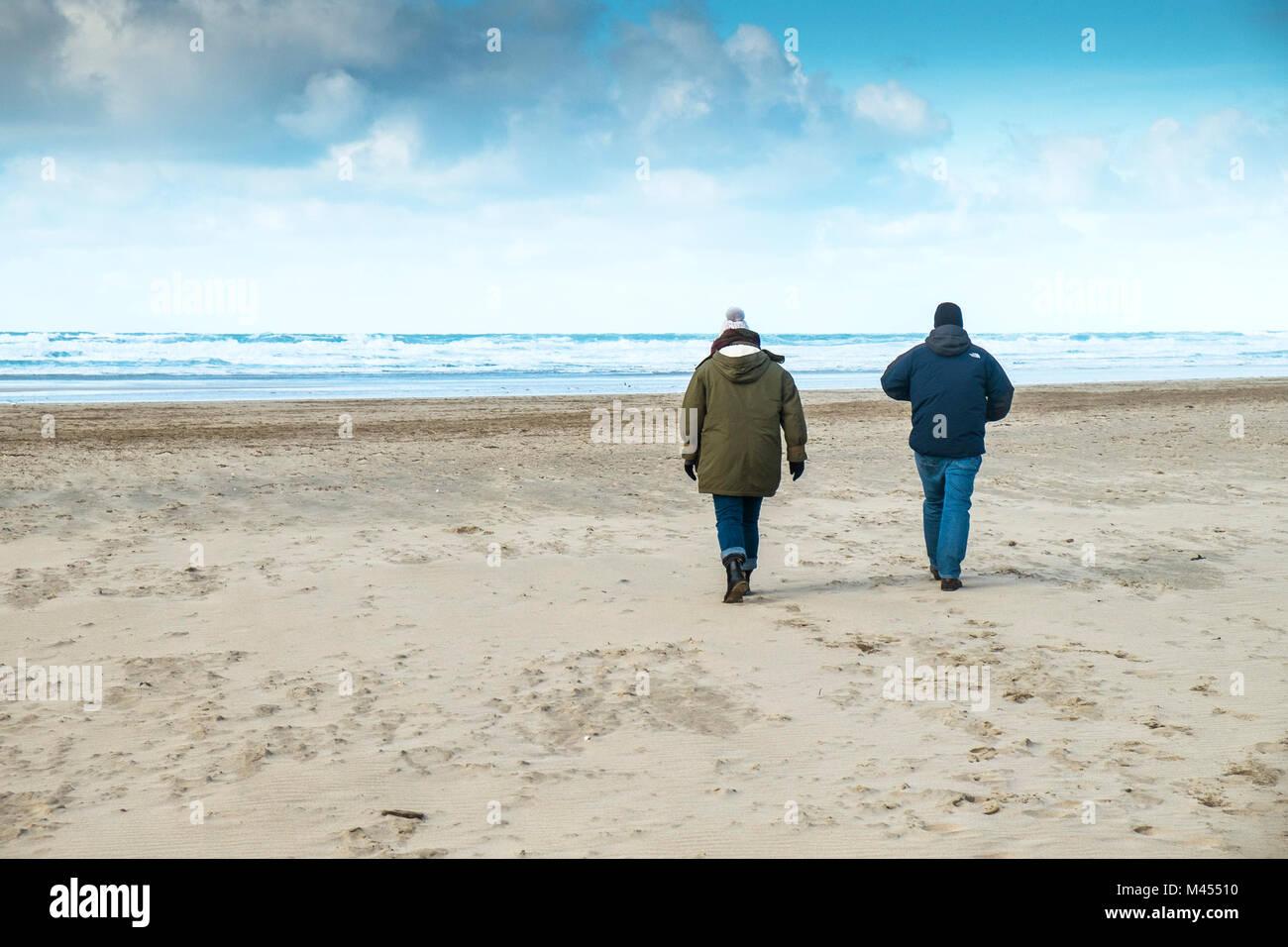 Zwei Menschen gehüllt vor dem kalten Wetter zu Fuß am Strand. Stockbild
