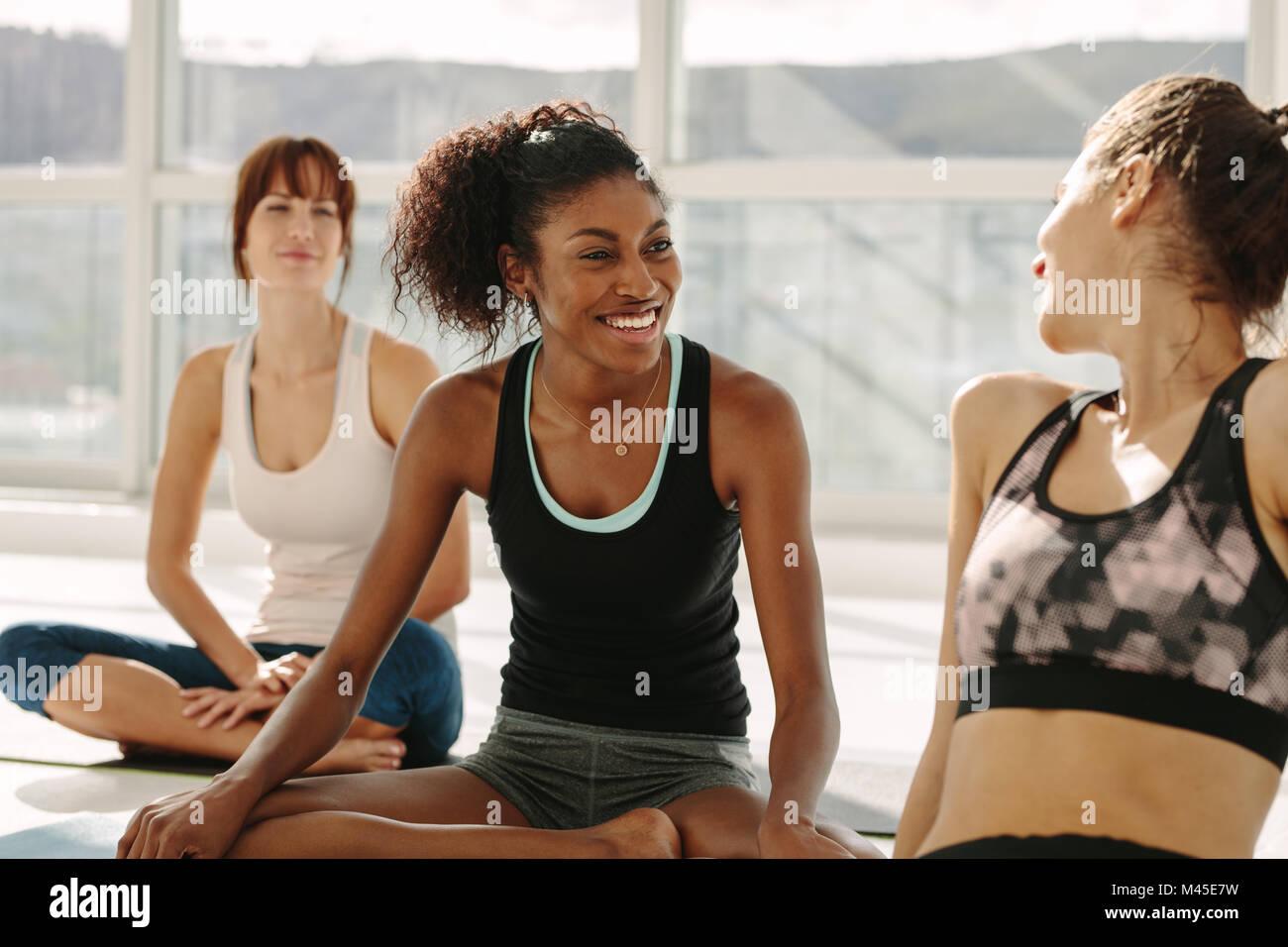 Junge weibliche entspannend und mit dem Sprechen, nachdem Training Session. Weibliche Freunde während Yoga Stockbild