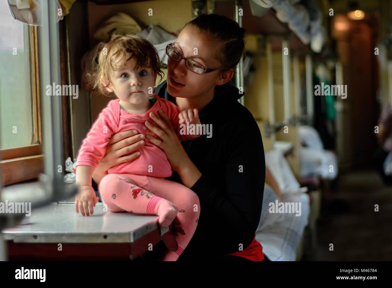 Eine junge Mutter fährt in Gläser zusammen mit einer