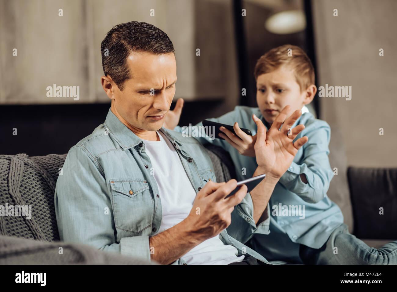 Besetzt Vater seinen Sohn bittet um Aufmerksamkeit Bürsten Stockfoto