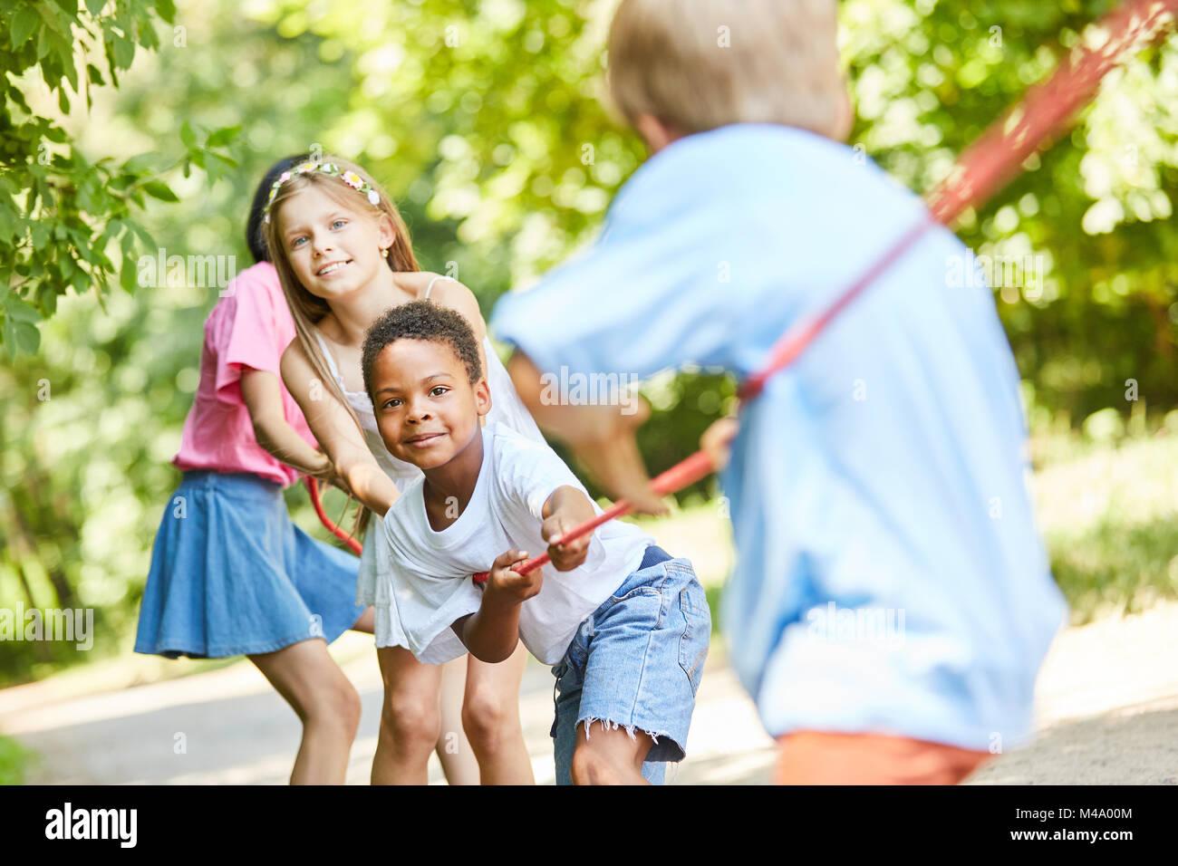 Gruppe von Kindern in Tauziehen Wettbewerb als starkes Team in der Natur Stockbild