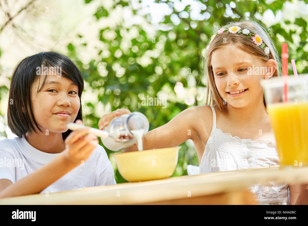 Zwei Mädchen essen, Getreide und Milch trinken zum Frühstück im Camp Stockbild