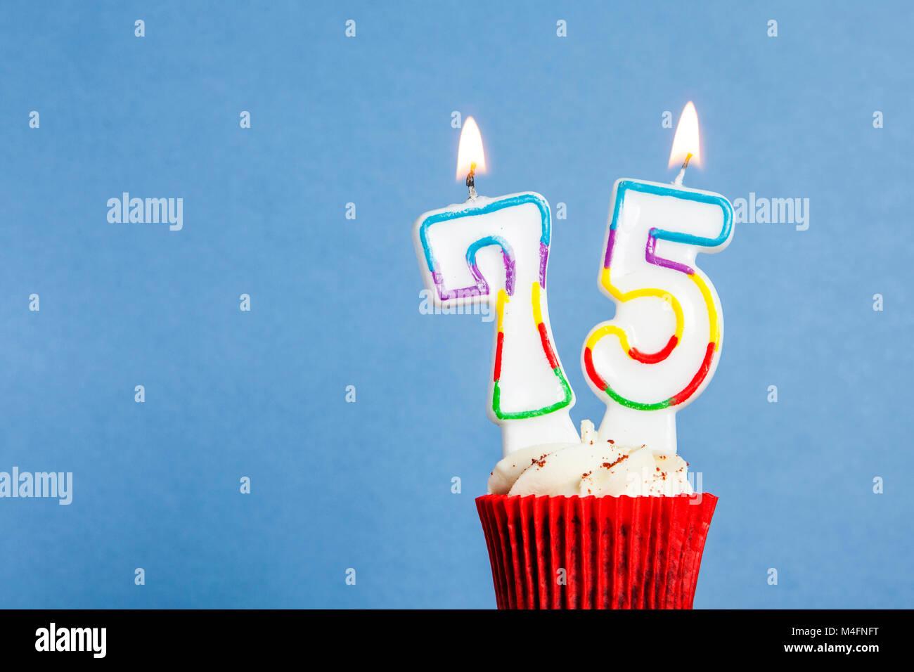 Nummer 75 Geburtstag Kerze In Eine Cupcake Vor Einem Blauen Hintergrund Stockbild