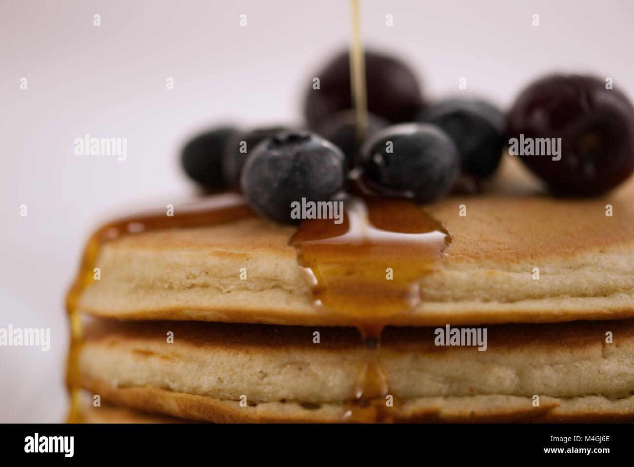 Frühstück Pfannkuchen mit Blaubeeren, Kirschen und Ahornsirup auf weißem Hintergrund mit sehr geringer Stockbild