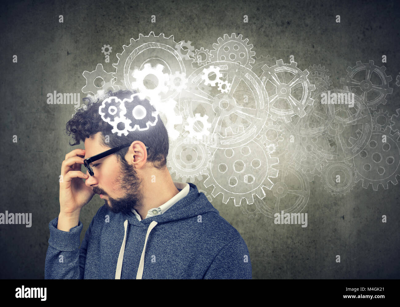 Nachdenklicher junger Mann auf der Suche nach einer Lösung mit Getriebe über seinem Kopf Stockbild